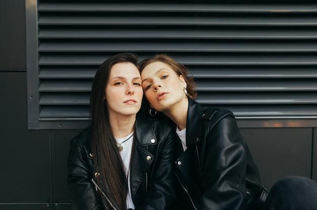 Portret van 2 modellen in leren jassen op donkere muur
