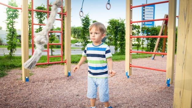 Portret van 3 jaar oud die op de speelplaats speelt en probeert op het grote touw in het park te klimmen