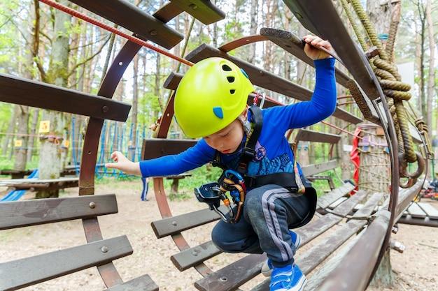 Portret van 3 jaar oude jongen die helm en het beklimmen draagt