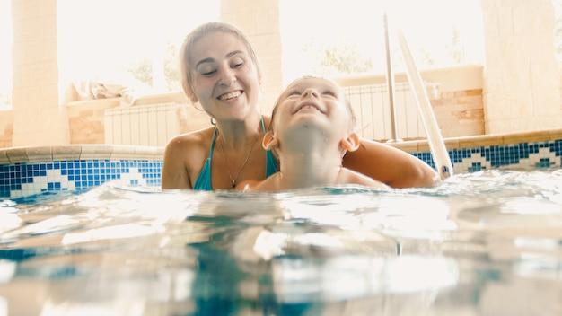 Portret van 3 jaar oude peuterjongen met jonge moeder die in het binnenbad zwemt. kind leren zwemmen en sporten. familie genieten en plezier maken in het water