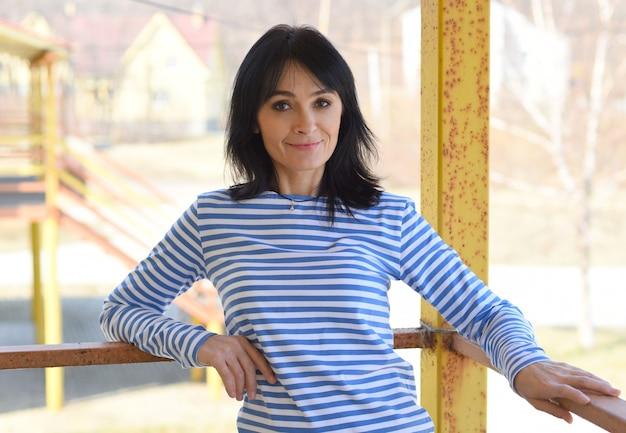 Portret van 45 jaar oude russische vrouw die en voorzijde glimlacht kijkt
