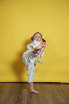 Portret van 5-jarige kaukasisch meisje in kimono karate beoefenen tegen gele achtergrond thuis
