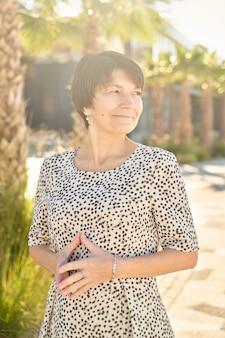 Portret van 50-jarige gelukkig blanke zakenvrouw poseren en lachend in het park, volwassen gezonde echte dame