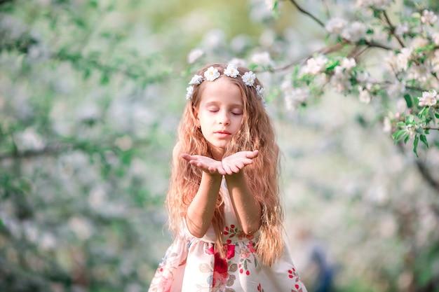 Portret van aanbiddelijk meisje in de bloeiende tuin van de kersenboom in openlucht