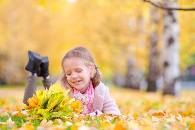 Portret van aanbiddelijk meisje met geel bladerenboeket in herfst. mooi glimlachend jong geitje dat op bladerentapijt ligt