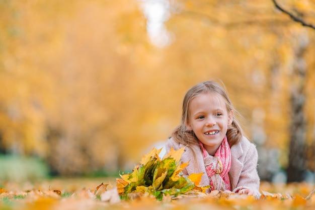 Portret van aanbiddelijk meisje met geel bladerenboeket in herfst