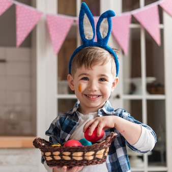 Portret van aanbiddelijke kleine jongen die een mand met eieren houdt