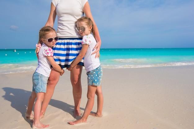 Portret van aanbiddelijke meisjes dichtbij momther bij exotisch strand op vakantie