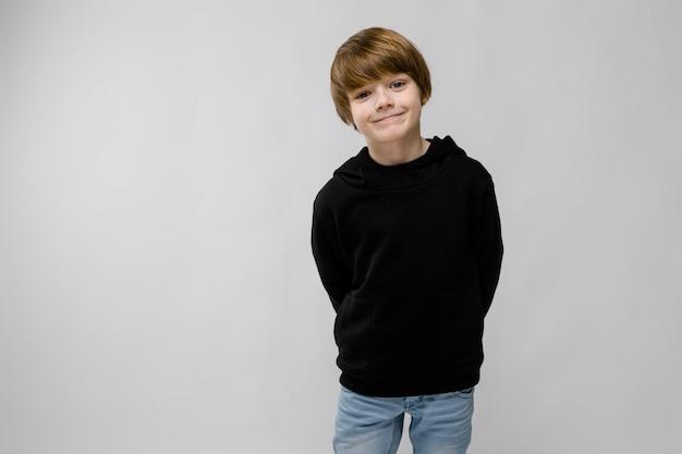 Portret van aanbiddelijke smilling kleine jongen die zich op grijze muur bevindt
