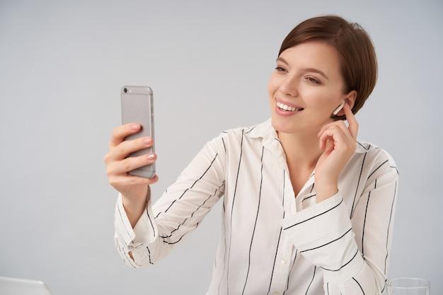 Portret van aangenaam uitziende jonge bruinharige vrouw met kort trendy kapsel glimlachend positief tijdens videochat met mobiele telefoon en koptelefoon, geïsoleerd op wit