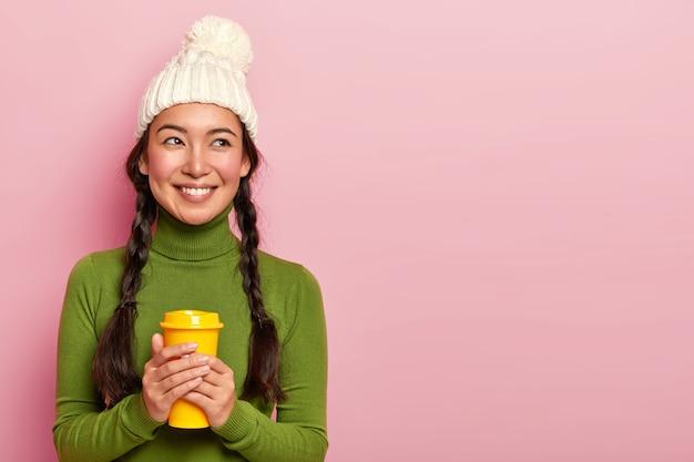 Portret van aangenaam uitziende jonge koreaanse vrouw houdt koffiekopje, verwarmt tijdens koude natte dag, draagt witte hoed met pompon en casual coltrui, heeft een glimlach op het gezicht, geïsoleerd over roze muur