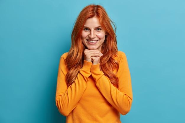 Portret van aangenaam uitziende roodharige jonge vrouw glimlacht gelukkig en houdt de handen onder de kin kijkt direct met tevreden uitdrukking gekleed in vrijetijdskleding.