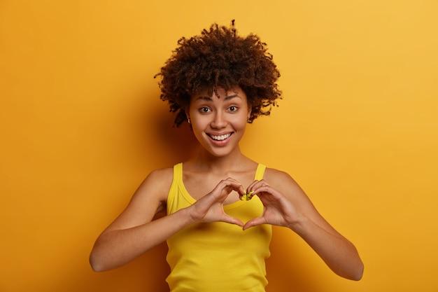 Portret van aangenaam uitziende vrouw maakt hartgebaar, zegt wees mijn valentijn, lacht positief, drukt liefde en zorg uit, werd verliefd op iemand, draagt een geel shirt, staat alleen binnen.