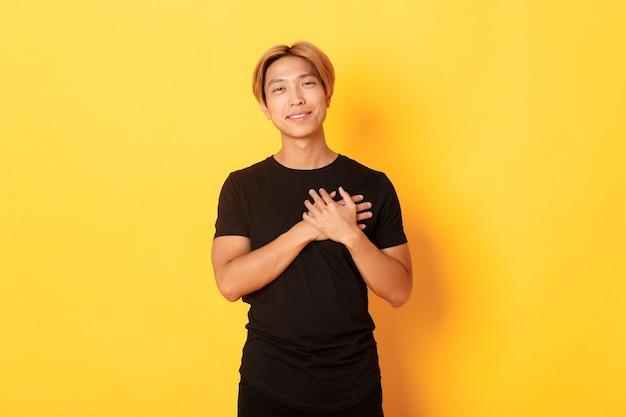 Portret van aangeraakte knappe aziatische man hand in hand op hart en glimlachend gevleid, gele muur.