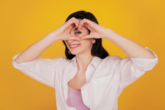 Portret van aanhankelijk meisje toont hartgebaar dekkingsoog op gele achtergrond