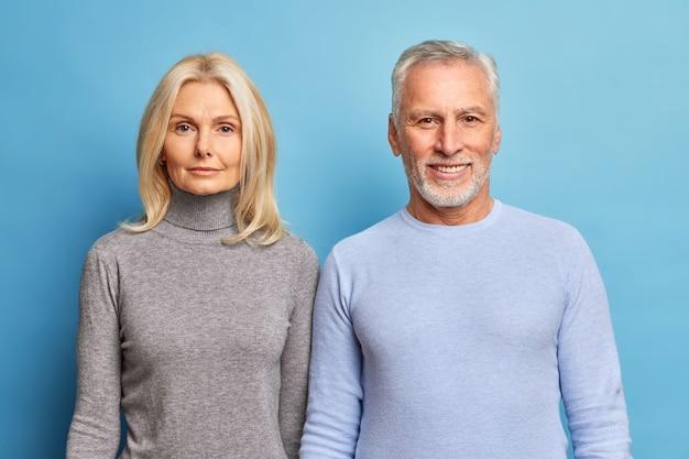 Portret van aanhankelijke bejaarde man en vrouw gekleed in vrijetijdskleding kijken vol vertrouwen naar voren