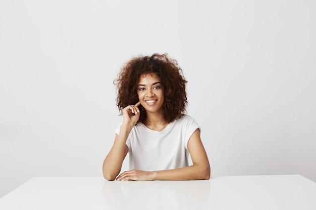 Portret van aantrekkelijk afrikaans meisje dat over witte muur glimlacht