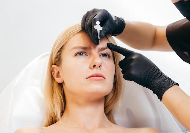 Portret van aantrekkelijk blonde model die injectie in voorhoofd maakt