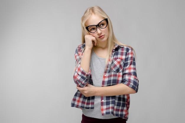 Portret van aantrekkelijk droevig zoet aanbiddelijk blondetienermeisje die in geruite kleren in glazen hand houden dichtbij haar gezicht op grijs
