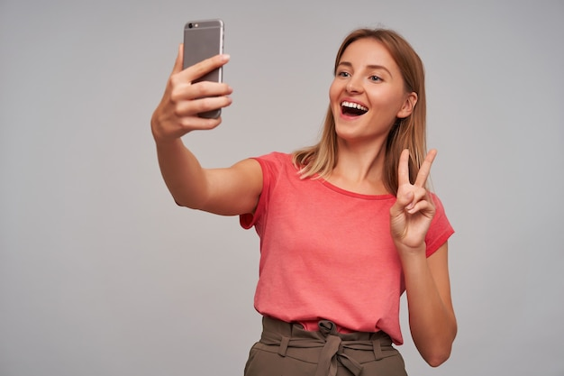 Portret van aantrekkelijk, gelukkig volwassen meisje met blond haar. ik draag een roze t-shirt en een bruine rok. selfie maken en vredesteken tonen, breed glimlachend over grijze muur