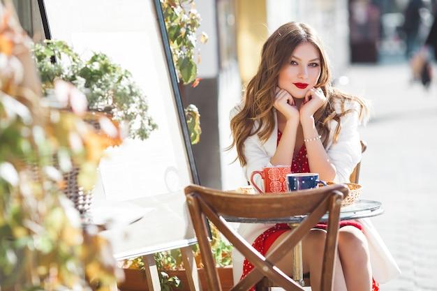 Portret van aantrekkelijk jong meisje in openlucht. mooie stedelijke dame die camera bekijkt. vrouw met rode lippen.
