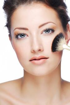 Portret van aantrekkelijk jong volwassen vrouwen schoonmakend gezicht na het aanbrengen van samenstelling