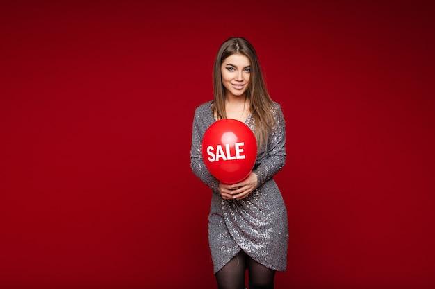 Portret van aantrekkelijk kaukasisch donkerbruin meisje in cocktailkleding met een rode luchtballon