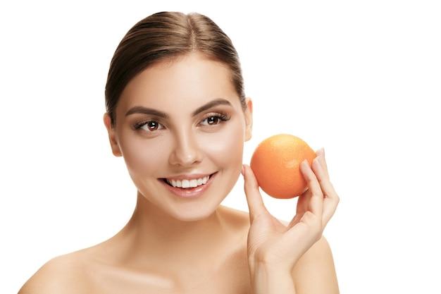 Portret van aantrekkelijk kaukasisch glimlachend houdend een oranje die vrouw op wit wordt geïsoleerd
