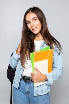 Portret van aantrekkelijk leuk jong studentenmeisje dat op witte muur wordt geïsoleerd