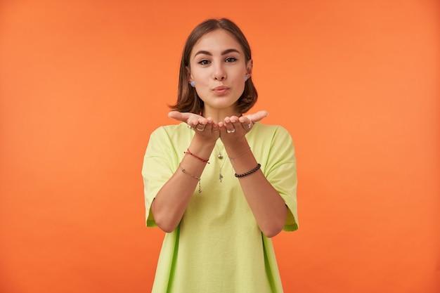Portret van aantrekkelijk, leuk ogend meisje met kort donkerbruin haar, een kus verzenden, verleidelijk groen t-shirt, armbanden en ringen dragen