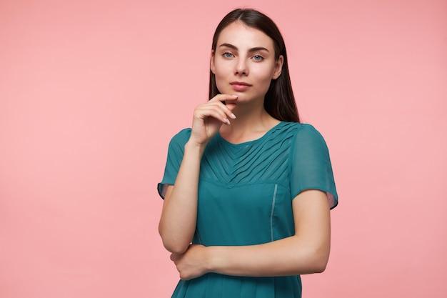 Portret van aantrekkelijk, leuk ogend meisje met lang donkerbruin haar. handen vouwen op een borst en haar kin aanraken. smaragdgroene jurk dragen. kijken geïsoleerd over pastel roze muur