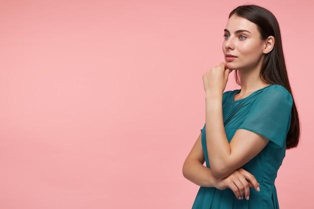 Portret van aantrekkelijk, leuk ogend meisje met lang donkerbruin haar. handen vouwen op een borst en haar kin aanraken. smaragdgroene jurk dragen. kijkend naar links op kopie ruimte over pastelroze muur