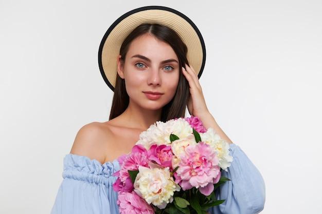 Portret van aantrekkelijk, leuk ogend meisje met lang donkerbruin haar. het dragen van een hoed en een blauwe jurk. boeket bloemen vasthouden en haar haar aanraken. kijken geïsoleerd over witte muur