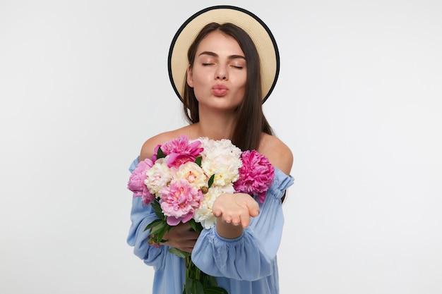 Portret van aantrekkelijk, leuk ogend meisje met lang donkerbruin haar. het dragen van een hoed en een blauwe jurk. een boeket bloemen vasthouden en een kus sturen. tribune geïsoleerd over witte muur