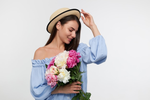 Portret van aantrekkelijk, leuk ogend meisje met lang donkerbruin haar. het dragen van een hoed en een blauwe mooie jurk. een boeket bloemen vasthouden en haar hoed aanraken. kijken naar beneden geïsoleerd over witte muur