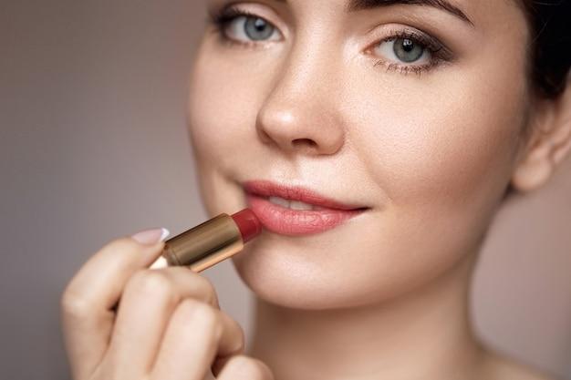 Portret van aantrekkelijk meisje dat haar lippen rouging close-up. ze houdt rode lippenstift vast. haar mond is zachtjes open.