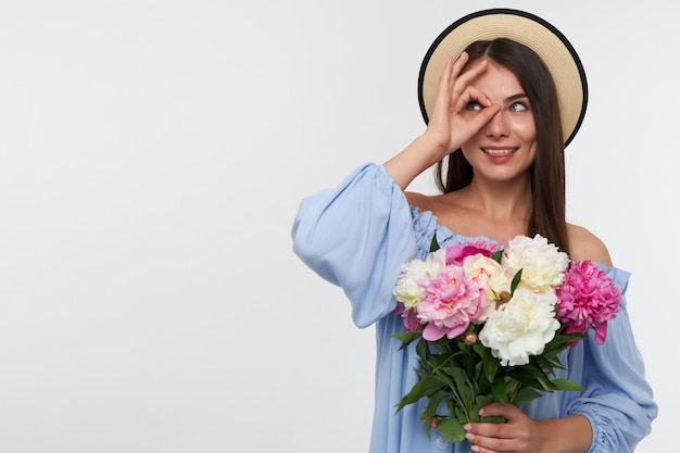 Portret van aantrekkelijk meisje met lang donkerbruin haar. het dragen van een hoed en een blauwe jurk. houd een boeket prachtige bloemen vast en kijk door de vingers naar links naar de kopie ruimte over een witte muur