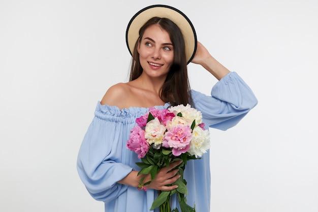 Portret van aantrekkelijk meisje met lang donkerbruin haar. het dragen van een hoed en een blauwe mooie jurk. een boeket bloemen vasthouden en een hoed aanraken. kijkend naar links op kopie ruimte over witte muur