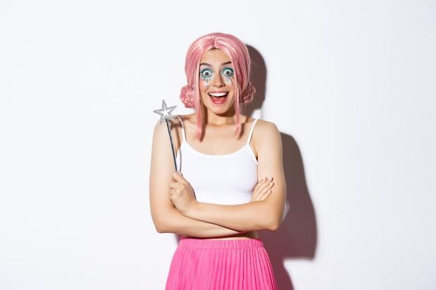Portret van aantrekkelijk meisje met roze pruik en lichte make-up, verkleed als een fee voor halloween-feest, met toverstaf en glimlachend.