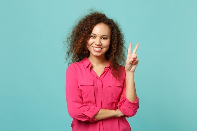 Portret van aantrekkelijk mooi afrikaans meisje in vrijetijdskleding die overwinningsteken toont dat op blauwe turkooizen muurachtergrond in studio wordt geïsoleerd. mensen oprechte emoties, lifestyle concept. bespotten kopie ruimte.