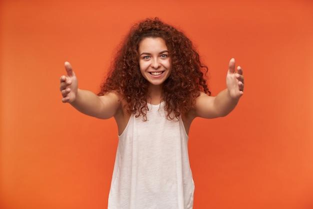 Portret van aantrekkelijk, mooi roodharig meisje met krullend haar. witte off-shoulder blouse dragen. spreid haar armen en probeer je te omhelzen. geïsoleerd over oranje muur