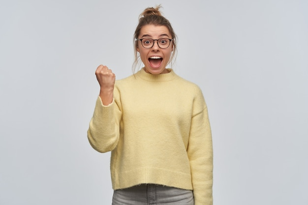 Portret van aantrekkelijk, opgewonden meisje met blond haar dat in broodje wordt verzameld. gele trui en bril dragen. bal haar vuist en vier succes. kijkend naar de camera, geïsoleerd over witte muur