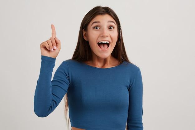 Portret van aantrekkelijk, opgewonden meisje met donker lang haar, gekleed in een blauwe trui