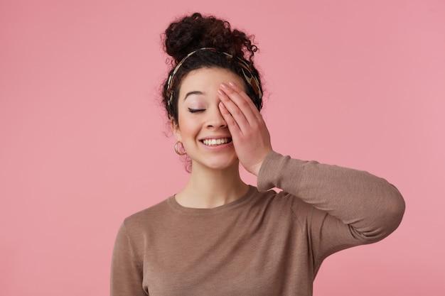 Portret van aantrekkelijk, positief meisje met donker krullend haarbroodje. met hoofdband, oorbellen en bruine trui. heeft make-up. sluit een oog met de handpalm