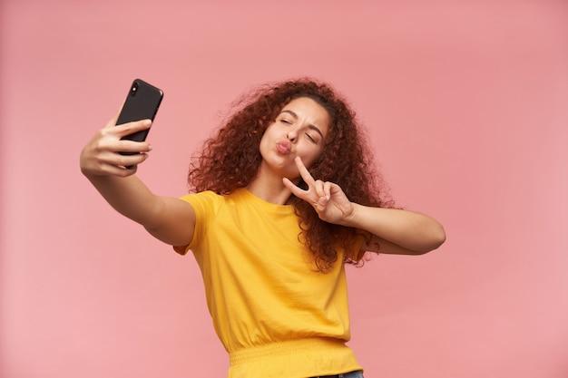 Portret van aantrekkelijk, roodharig meisje met krullend haar dat gele t-shirt draagt