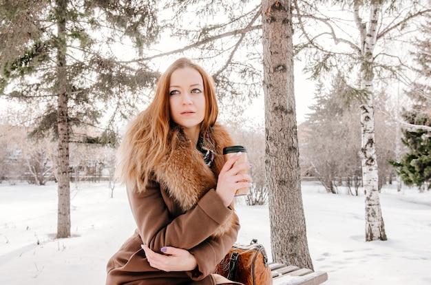 Portret van aantrekkelijk roodharigemeisje in de winterpark
