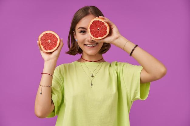 Portret van aantrekkelijk, schattig meisje met kort donkerbruin haar. houd grapefruit voor haar oog en bedek één oog. staande over paarse muur. het dragen van een groen t-shirt, ketting, bretels en armbanden