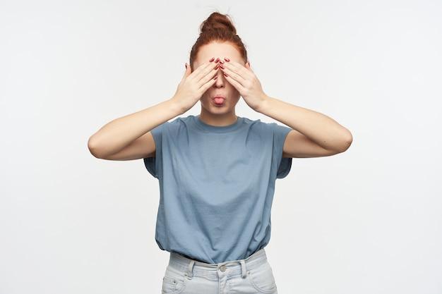 Portret van aantrekkelijk, speels roodharig meisje met haar dat in een knotje wordt verzameld. blauw t-shirt en spijkerbroek dragen. bedek haar ogen met handpalmen en laat een tong zien. tribune geïsoleerd over witte muur