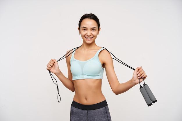 Portret van aantrekkelijk, sportief aziatisch meisje met donker lang haar. sportkleding dragen en een springtouw om haar nek houden. heb een vrolijke glimlach. kijken naar de camera geïsoleerd op witte achtergrond