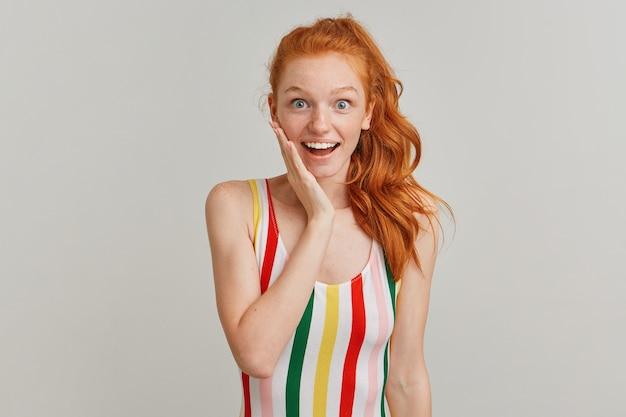 Portret van aantrekkelijk, verbaasd meisje met gember paardenstaart en sproeten, gestreepte kleurrijke zwembroek dragen